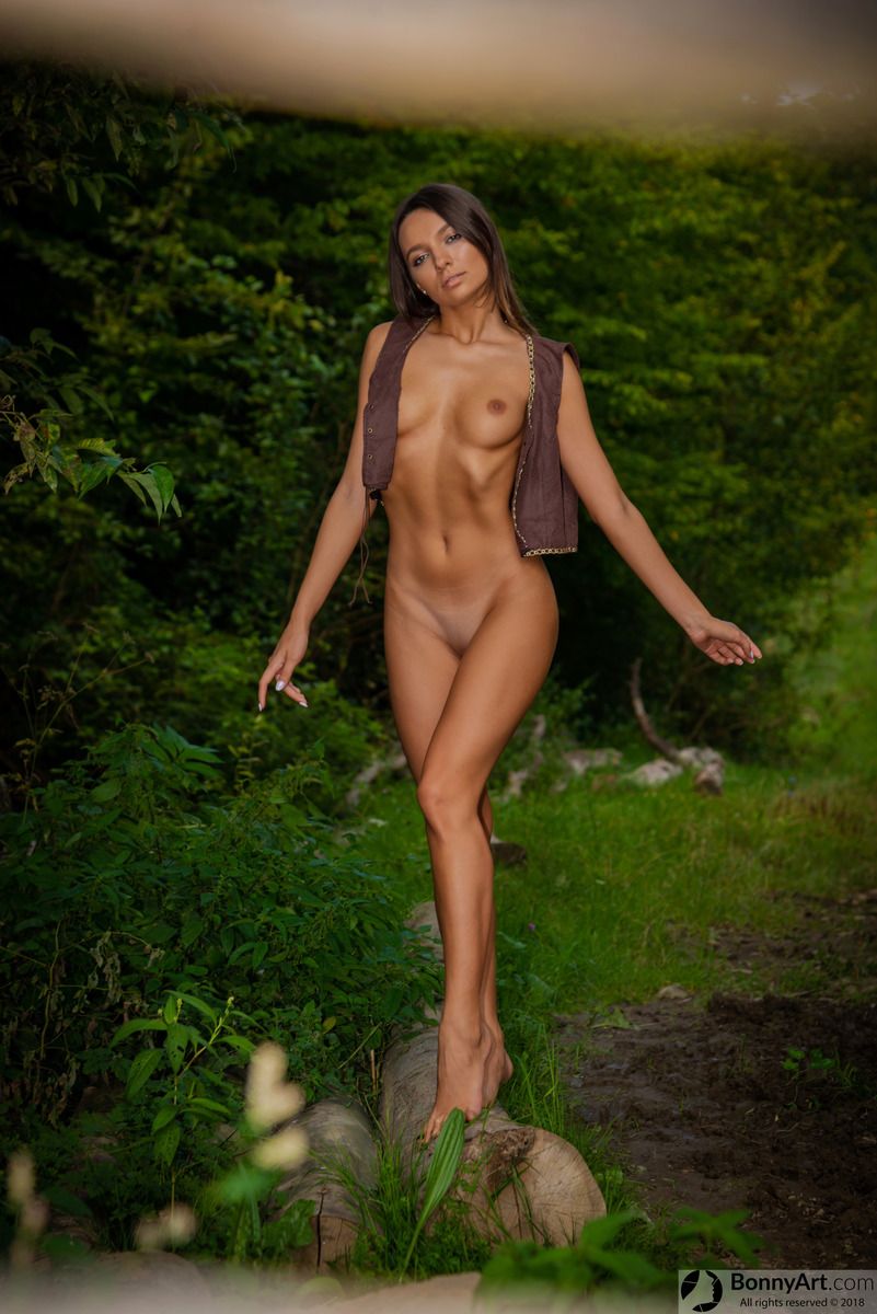 Beautiful Young Woman Walking on a Log in the Woods