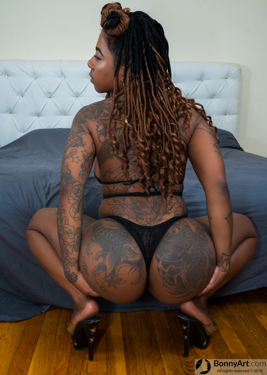 Tattooed Black Bootylicious Woman Thong Squatting