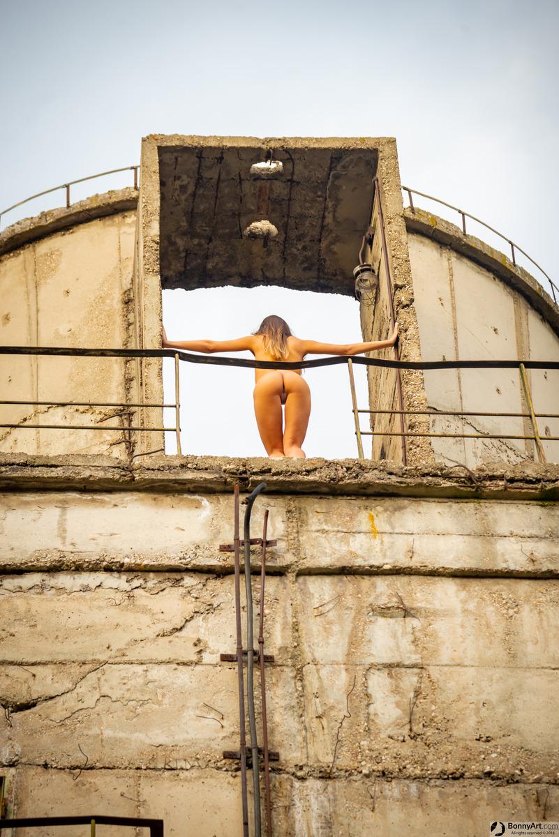 Nude Model Bending Over Concrete Building